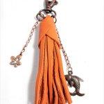 Bijou de sac pompon cuir de vachette coloris orange.