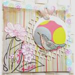 Carte d'amitiés  en scrap oiseau dans son nid de fleurs suspendu sur fond multicolore rose, jaune, fris graphique