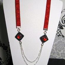 collier long rouge et noir sur velours rouge