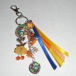 Porte clés/Bijoux de sac poupée orange avec perles et rubans multicolores
