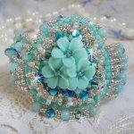 Bracelet Blue Flowers Haute-Couture brodé avec des Cristaux de Swarovski, un cabochon en résine, des perles rondes en satin, des rocailles avec une chaînette et un fermoir en Argent 925/1000